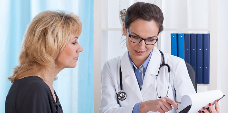 Image of a female doctor reading a chart to an adult female patient in Foley, AL Health Insurance